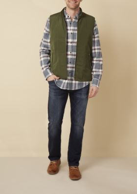 Man wearing an olive vest jacket over plaid shirt and jeans