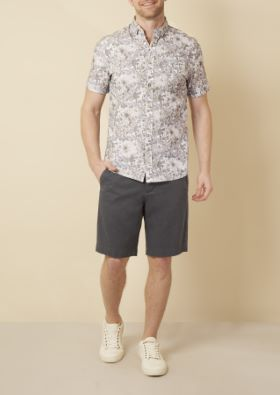Man wearing floral print short sleeve button up and dark shorts
