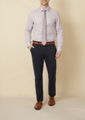 Man wearing light shirt and tie with dark chinos