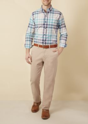 Man wearing light colored plaid dress shirt, khaki pants with belt