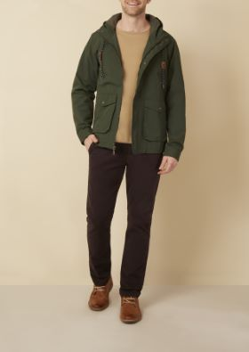 Man wearing green hooded jacket over tan sweater and dark brown pants