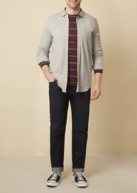 Man wearing a light colored shirt over maroon striped long sleeve and dark blue jeans
